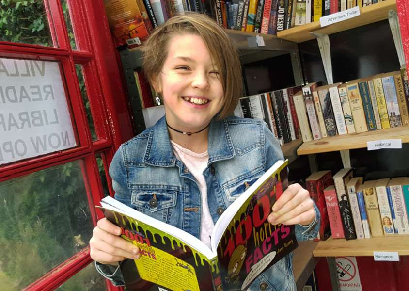 11-year-old Aisling Giltinan calls in for a read at the new Stathern phone box library in the village EMN-161128-125934001