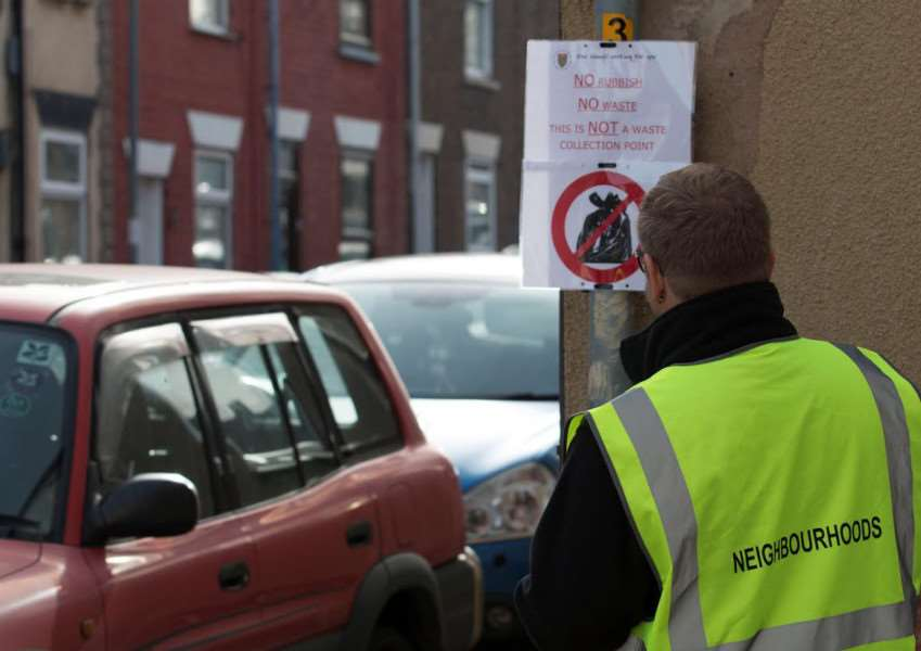Enforcement officer puts up a warning sign in Grantley Street, on the corner of Railway Terrace.
