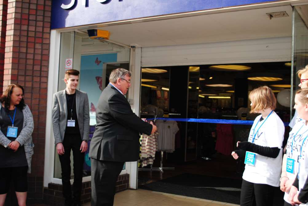 Deputy mayor Bruce Wells cuts the ribbon to open the store.