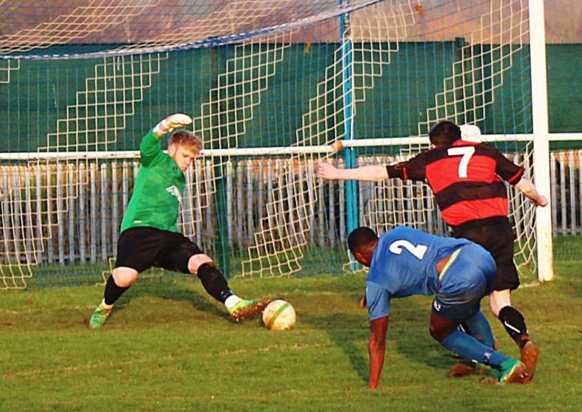 Harrowby keeper Sam Andrew saves with an outstretched leg.