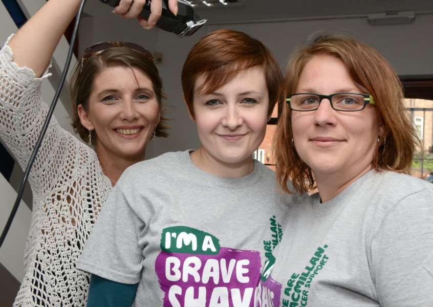 Toni Angeloni, of Toni's Barber Shop, prepares to shave the heads of Heather Paddison and Natasha Holmes for Brave the Shave.