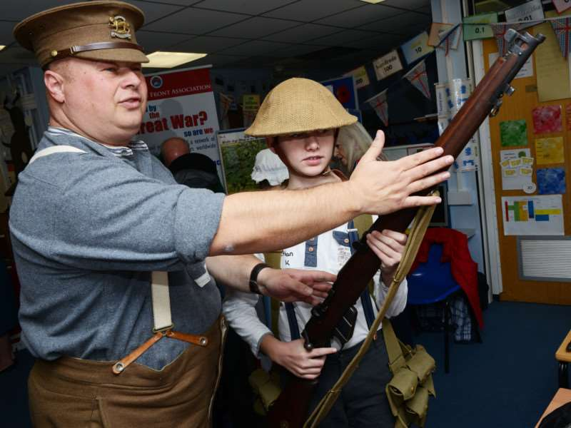 Andy Ball demonstrates some WW1 weapons to pupil Ethan Kemp.