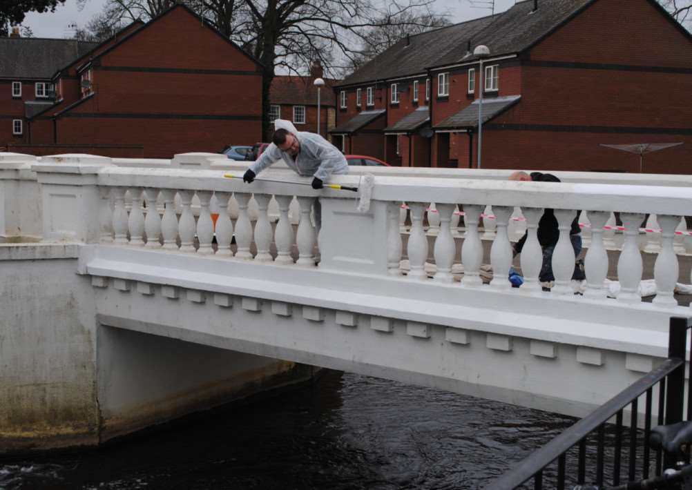 Darren Abbott paints the White Bridge in Wyndham Park.