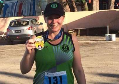 Suzanne Britz proudly displays her finishers' medal.