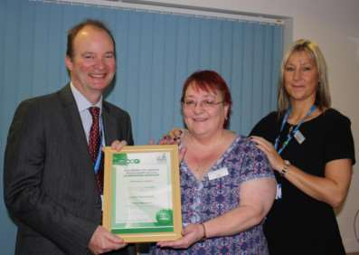 Trust chief executive, Dr John Brewin, presents AIMS certificate to Ashley House unit manager, Carol Fogg.