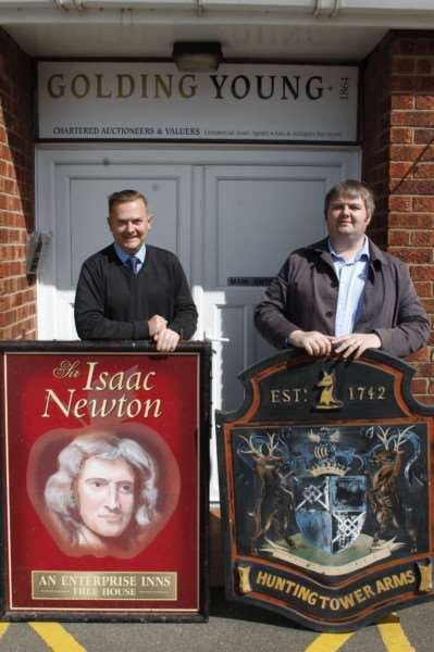 Auctioneers Craig Bewick and Andre Doubleday with two of the pub signs up for auction at Golding, Young and Mawer in Grantham.
