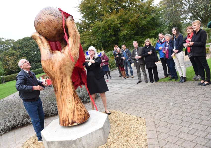 Mayor of Grantham Coun Linda Wootten unveils the apple sculpture in the sensory garden in Grantham with the help of John Knowles, chairman of Wyndham Park Forum.
