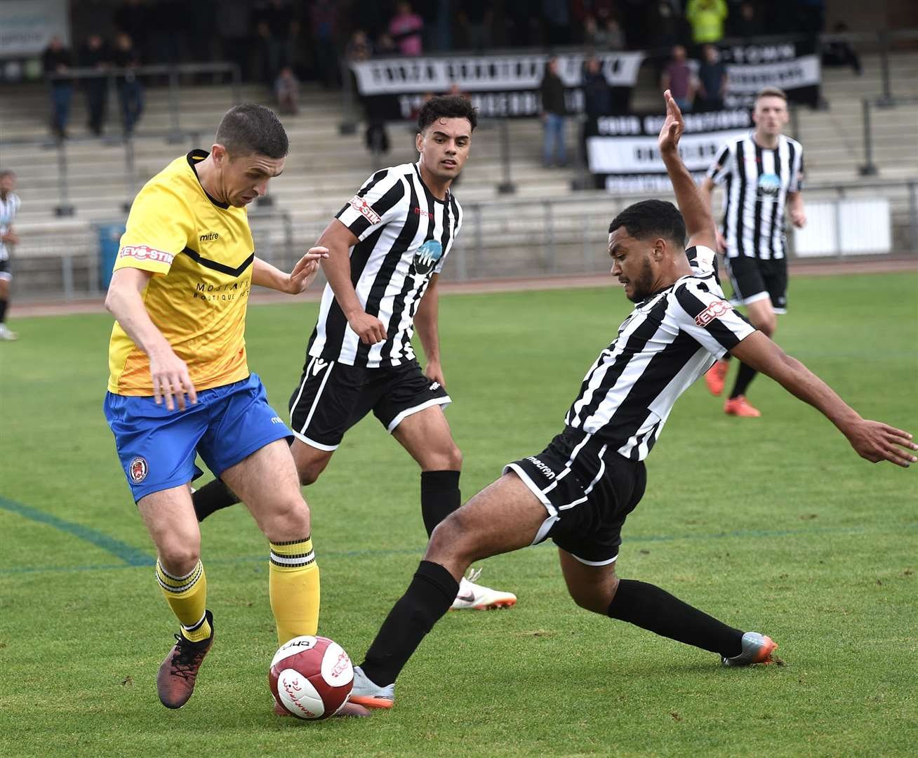Supported by Cenk Acar, Grantham Town's Ross Barrows tackles a Hyde United player on Saturday. Photo: Toby Roberts (4291626)