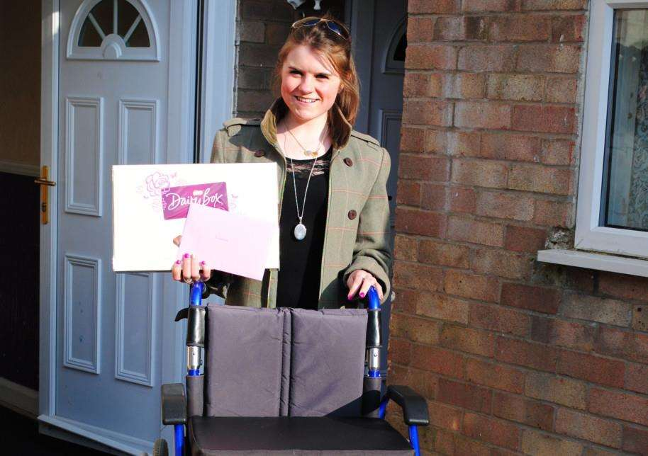 Lauren Farrow, 19, with the wheelchair she has purchased for Declan Nugent, 16, and thank you chocolates.