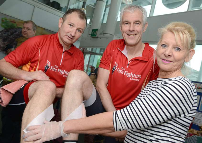 Firefighters Craig Tuck and Clive Baillie get their legs waxed by Jude Hall, of the Coloroom.